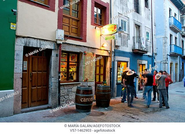 Group of young men in the street, by a typical tavern. Night view. Llanes, Asturias province, Spain