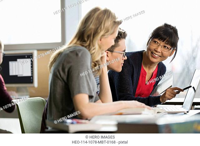 Professor and college students studying at laptop
