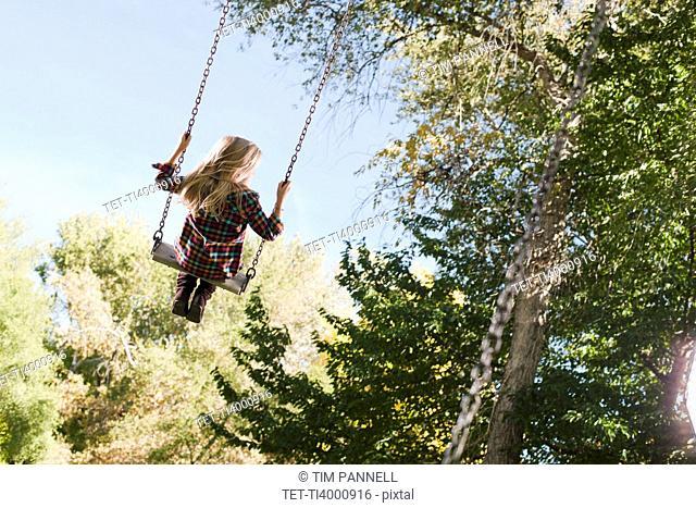 USA, Utah, girl 6-7 swinging on tree swing