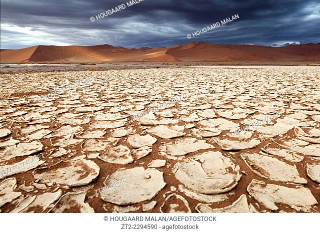 Landscape photo of the cracked pans below Sossusvlei's dunes under stormy skies. Sossusvlei, Namib Naukluft National Park, Namibia