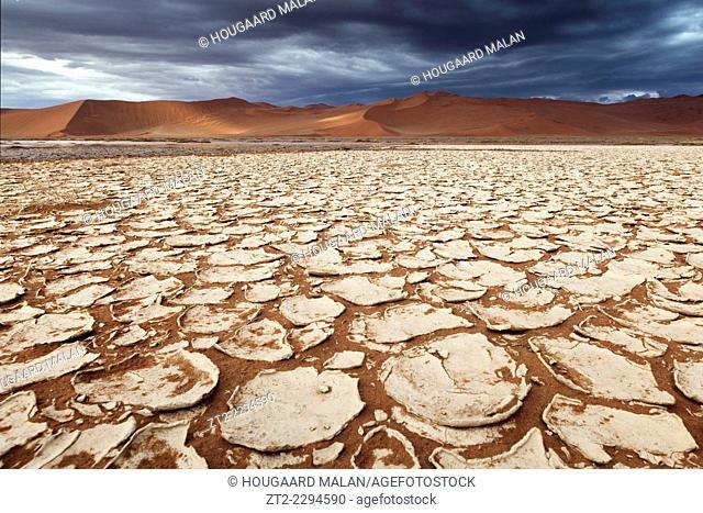 Landscape photo of the cracked pans below Sossusvlei's dunes under stormy skies. Sossusvlei, Namib Naukluft National Park, Namibia