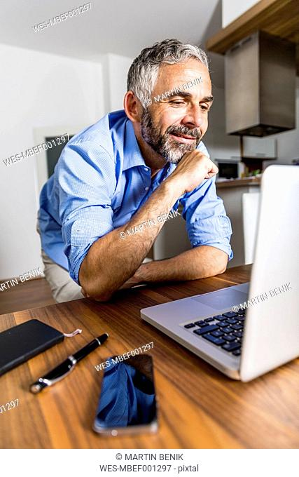 Portrait of smiling businessman at home office looking at his laptop