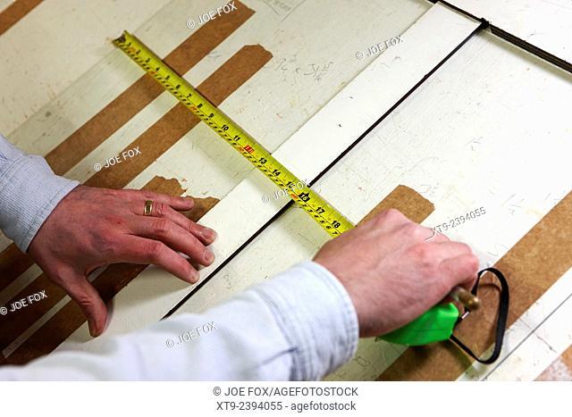 framer measuring glass for frame in a framing workshop