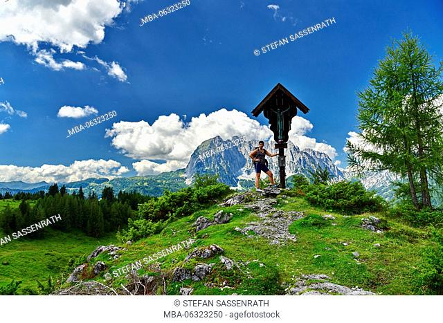 Young woman stands on a hill with cross