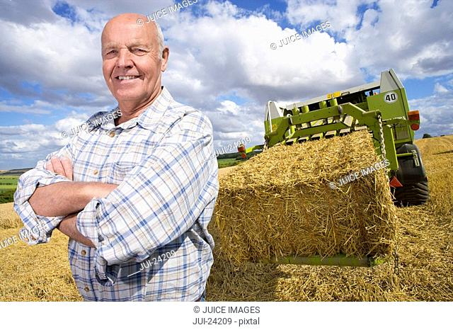 Portrait of smiling farmer standing in rural field near tractor and straw baler