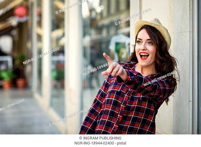 Young woman with beautiful blue eyes wearing plaid shirt and sun hat pointing with her finger. Girl in urban background