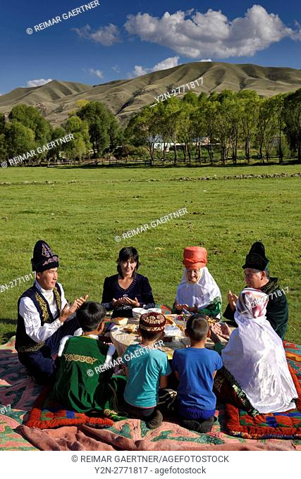 Kazakh family in traditional clothes praying before eating at a picnic in Saty Kazakhstan