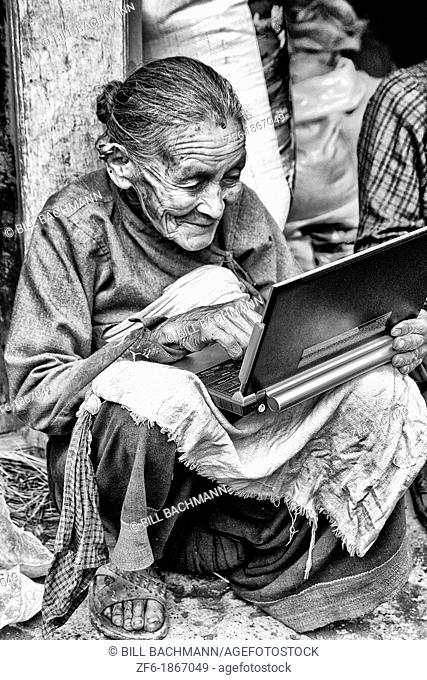 Great image of modern technology with old woman and new laptop computer in village of Bhaktapur a town near Kathmandu Nepal