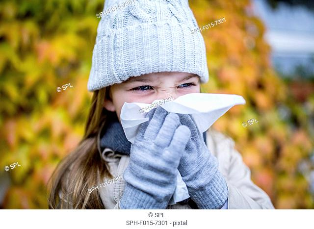 MODEL RELEASED. Young girl sneezing, close-up