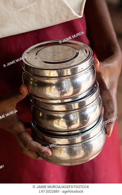 Hands hold tiffins which are used to hold lunches in India