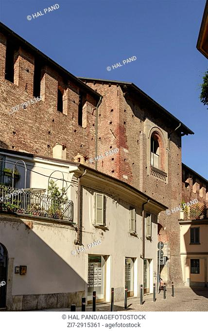 cityscape of small town with Renaissance castle wall looming over old houses, shot in a bright summer day at Vigevano, Pavia, Lombardy, Italy