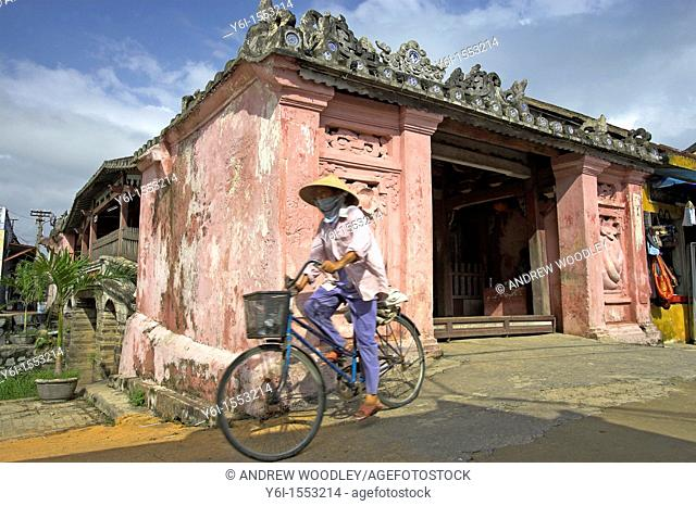 Conical hat woman on bicycle exits Japanese 17th century covered bridge Hoi An historic town Vietnam