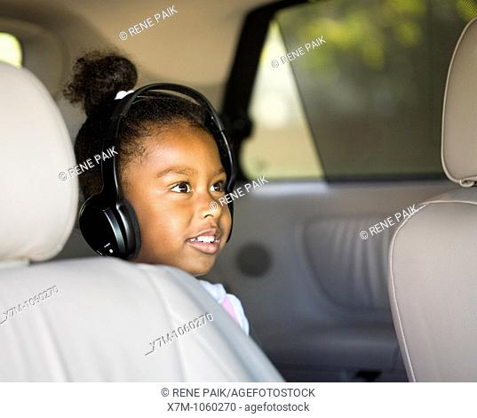Little girl watches a DVD in the minivan with headphones