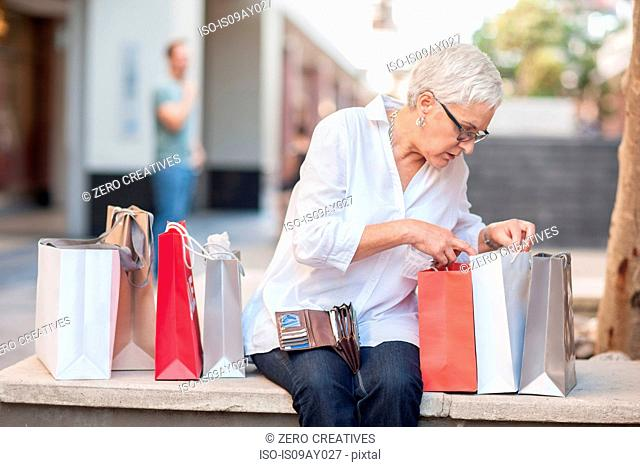 Mature woman peering into shopping bags at shopping mall