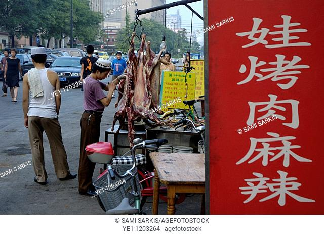 Young Muslim butcher selling meat in the street in the Muslim district of Daqingzhen Si in Xi'an, Shaanxi, China