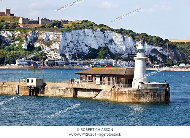 Northern cliffside of Dover on top of which is a partial view of Dover Castle. In the foreground is the Dover West End Breakwater Lighthouse, Dover