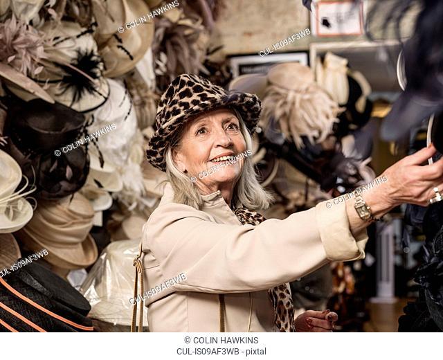Glamorous senior woman looking at hats