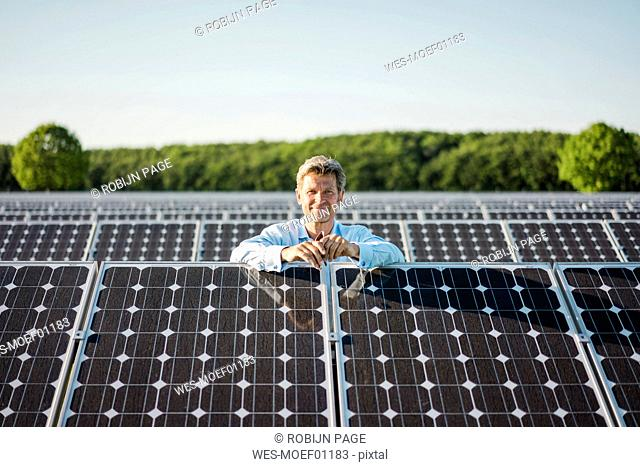 Smailing mature man standing in solar plant