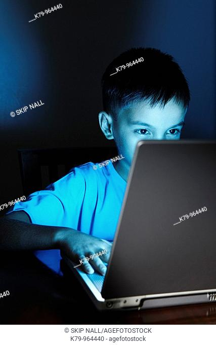 Young Asian boy using laptop at night