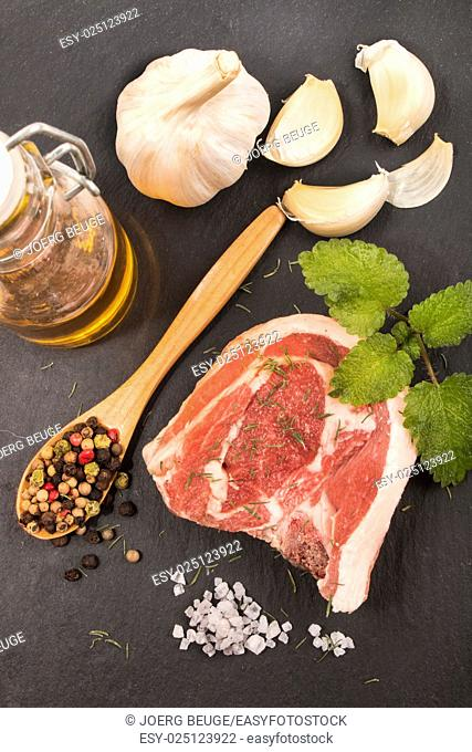 raw lamb chop with dried thyme, mint, garlic, olive oil in a bottle, coarse salt, peppercorn and wooden spoon on slate