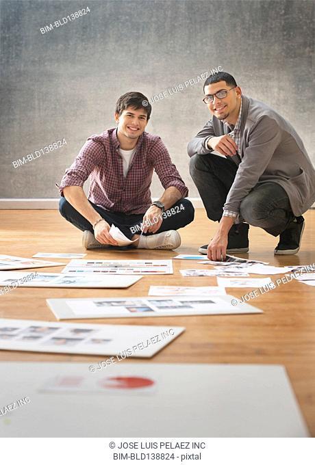 Hispanic businessmen spreading paperwork on office floor