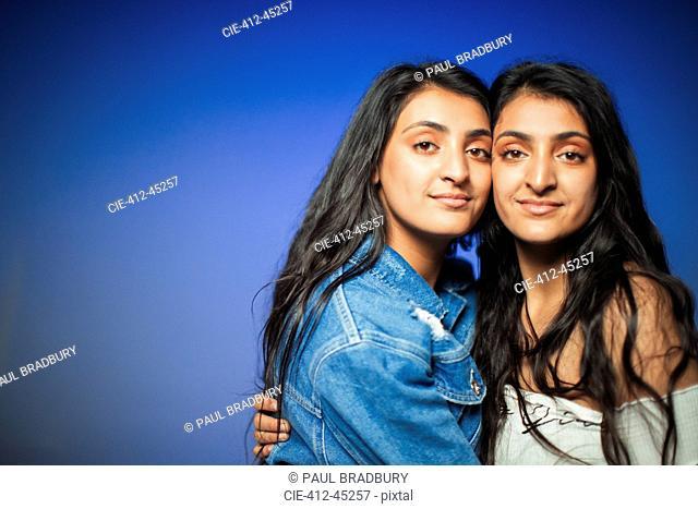 Portrait confident teenage twin sisters hugging