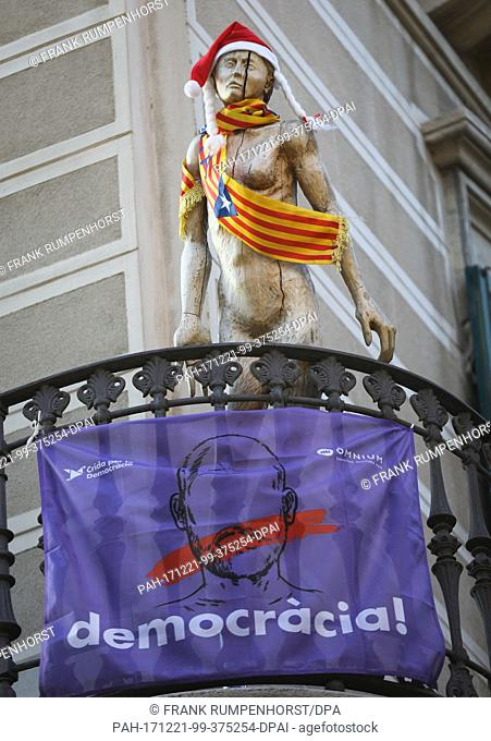 A wooden figure with a Santa Claus cap and a Catalan flag on the chest campaigns for the independence of Catalonia on a balcony in Barcelona, Spain