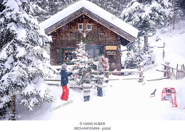 Austria, Altenmarkt-Zauchensee, family decorating Christmas tree at wooden house