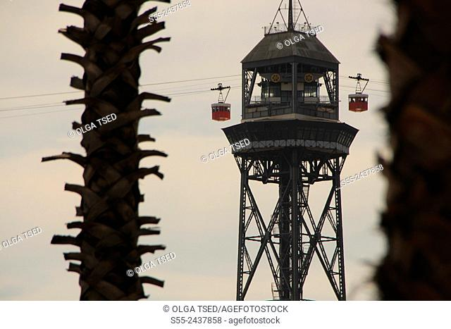 Barcelona cable car tower between palm trees. Maremagnum area, Port Vell, Barcelona, Catalonia, Spain