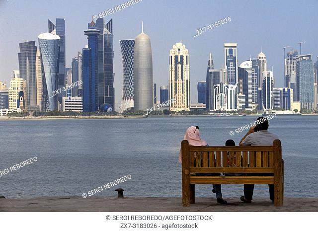 Local family looking the skyline with the skyscrapers in the financial area of Doha, the capital of Qatar in the Arabian Gulf country