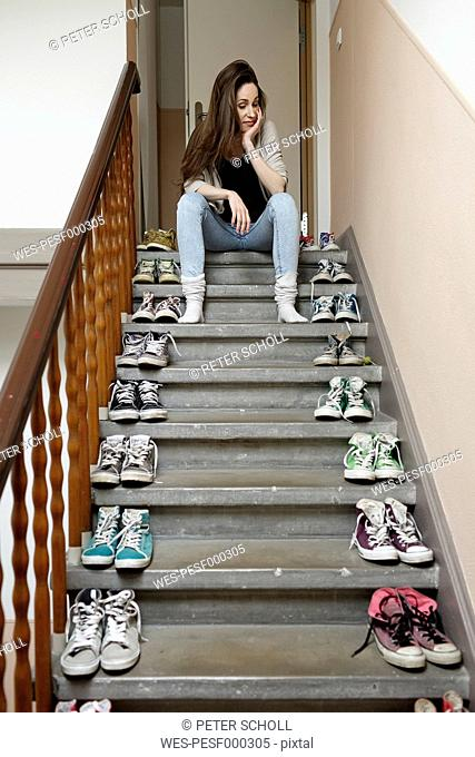 Young woman sitting on staircase with lots of shoes