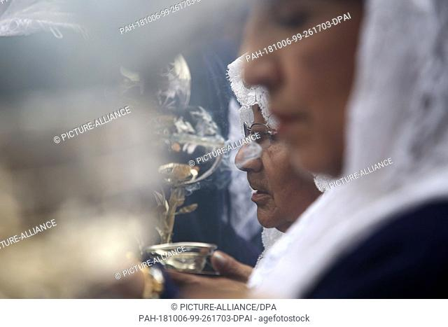 """06 October 2018, Peru, Lima: During a procession in honour of the """"""""Senor de los Milagros"""""""" (Lord of Miracles), a woman holds an incense burner"""