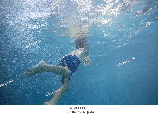 Boy swimming underwater in swimming pool