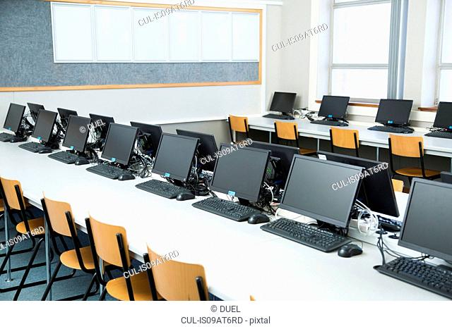 Empty classroom with rows of personal computers on desk