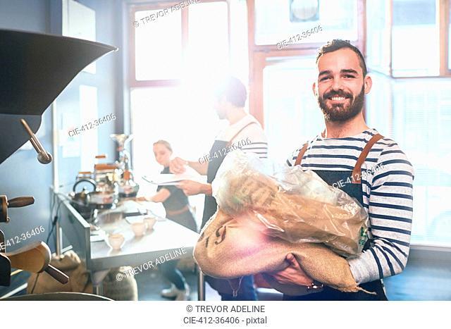 Portrait smiling, confident male coffee roaster