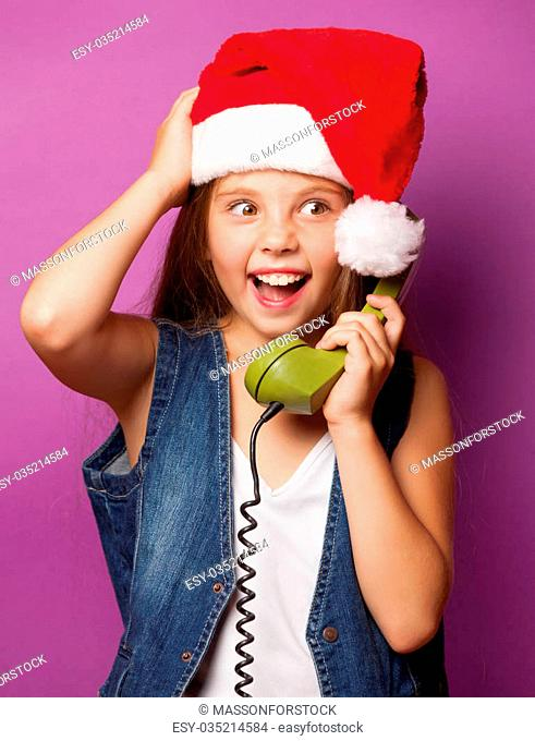 Beautiful young girl in red Santas hat with green handset on violet background