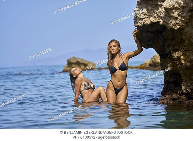 Greece, Crete, Chersonissos, women in bikini in sea, feeling sexy