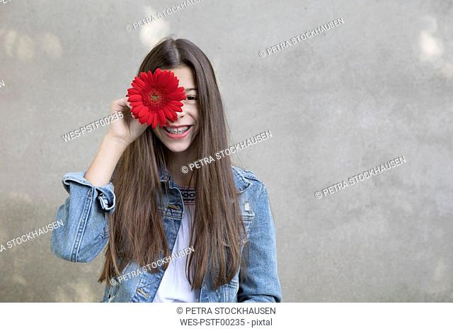 Portrait of laughing girl with flower head of red Gerbera