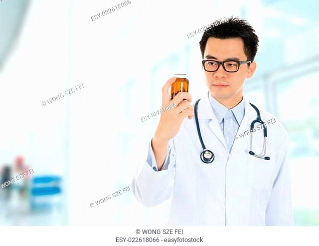 Asian doctor checking drugs inside hospital