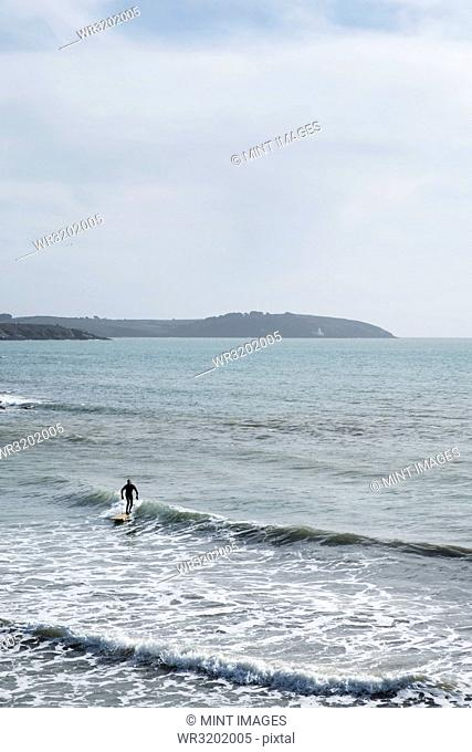 Surfer wearing wet suit riding ocean wave close to shore