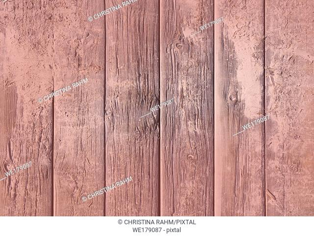 Weathered wood background texture. Old rugged planks with screws for background texture toned in Living Coral color