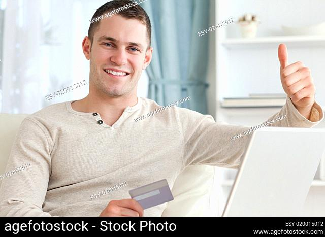 Smiling man shopping online with the thumb up