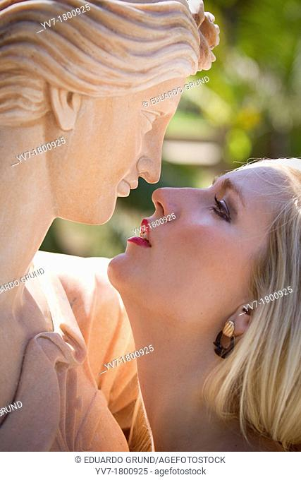 Young blonde girl kissing a sculpture