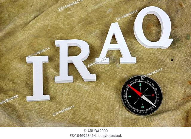 Sign IRAQ From Wood Letter And Magnetic Compass On The Weathered Backpack Or Military Camouflage Background