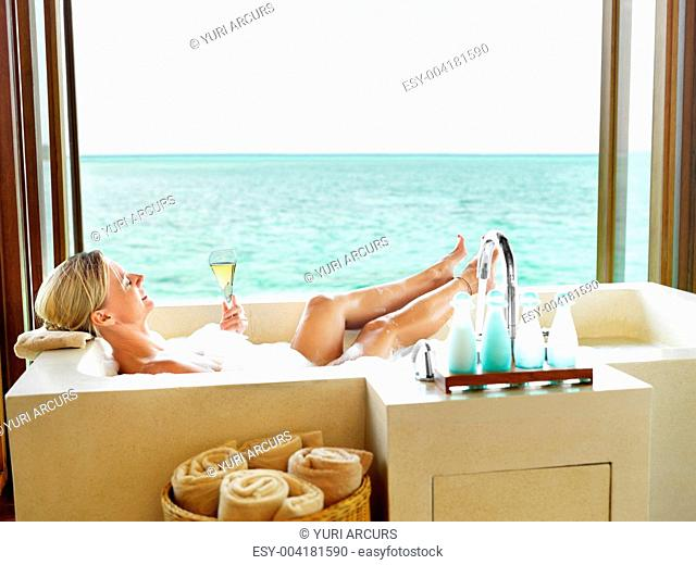 Portrait of relaxed mature woman with champagne in the bathtub enjoying good times