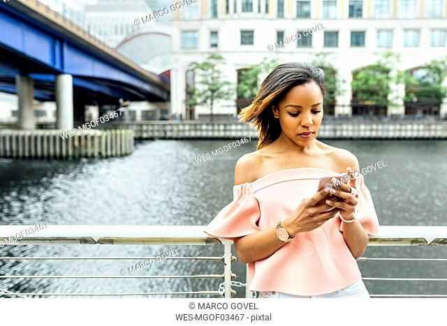 Woman sending messages with her smartphone in the city