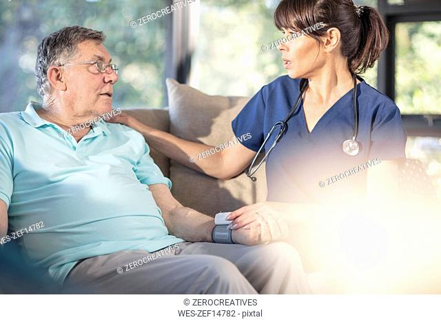 Nurse caring for of senior patient at home