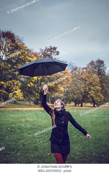 Happy young woman dancing with umbrella in autumnal park
