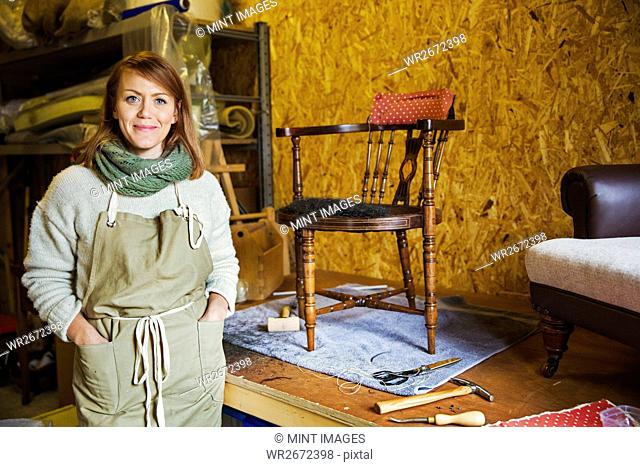 Upholstery workshop. A young woman with hands in her apron pockets. Work in progress