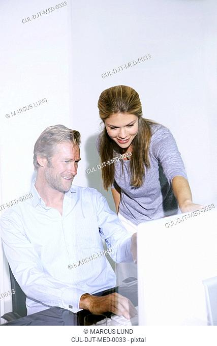 Man and woman in office at computer